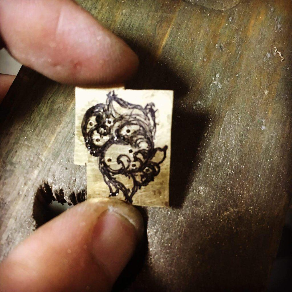 模様を切り抜くために真鍮板に穴を開ける