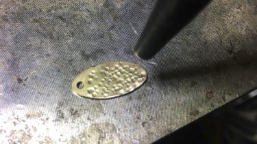 穴を開けた真鍮板に芋槌で模様を打っていく