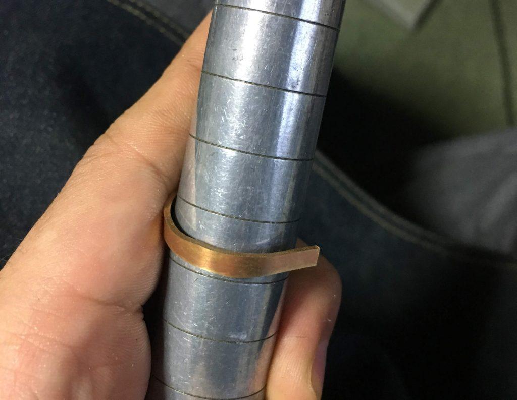 なました後にサイズ棒に押し付けて真鍮板を曲げる